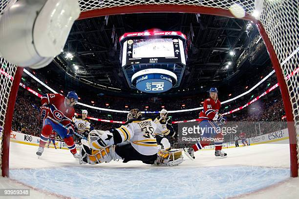 Tim Thomas of the Boston Bruins stops the puck in front of Mike Cammalleri and Andrei Kostitsyn of the Montreal Canadiens during the NHL game on...