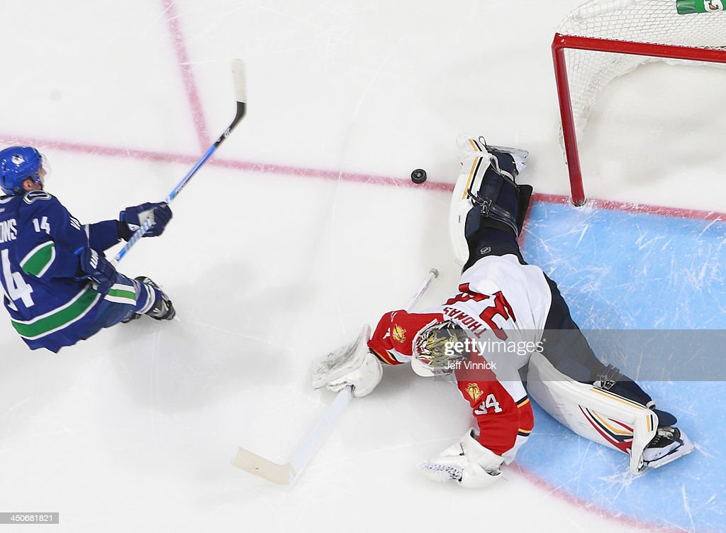Tim Thomas #34 of the Florida Panthers makes a shootout save on <a gi-track='captionPersonalityLinkClicked' href=/galleries/search?phrase=Alexandre+Burrows&family=editorial&specificpeople=592489 ng-click='$event.stopPropagation()'>Alexandre Burrows</a> #14 of the Vancouver Canucks during their NHL game at Rogers Arena on November 19, 2013 in Vancouver, British Columbia, Canada. Florida won 3-2 in a shootout.