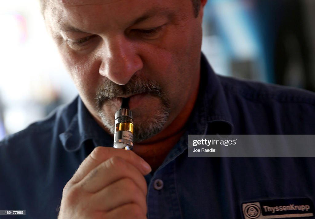 Tim Tranthem tries an electronic cigarette as he shops at the Vapor Shark store on April 24, 2014 in Miami, Florida. Brandon Leidel, CEO, Director of Operations Vapor Shark, said he welcomes the annoucement by the Food and Drug Administration that they are proposing the first federal regulations on electronic cigarettes, which would ban sales of the popular devices to anyone under 18 and require makers to gain FDA approval for their products.