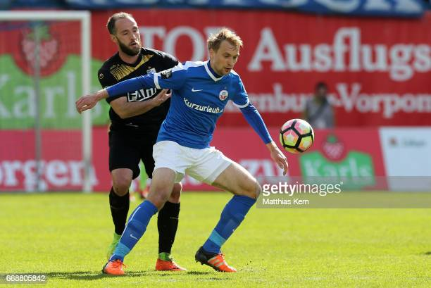 Tim Vaeyrynen of Rostock battles for the ball with Christopher Handke of Magdeburg during the third league match between FC Hansa Rostock and 1FC...