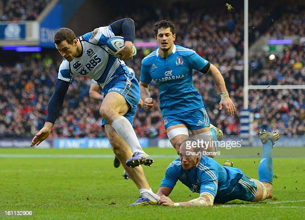 Tim Visser of Scotland breaks through the tackle of Sergio Parisse of Italy to score a try during the RBS Six Nations match between Scotland and...