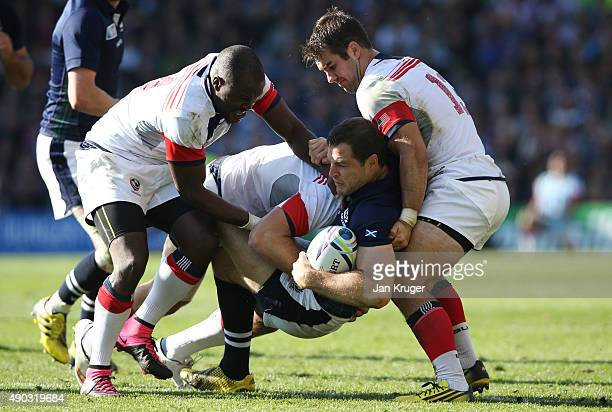 Tim Visser of Scotland is tackled by Takudzwa Ngwenya and Seamus Kelly of the United States during the 2015 Rugby World Cup Pool B match between...