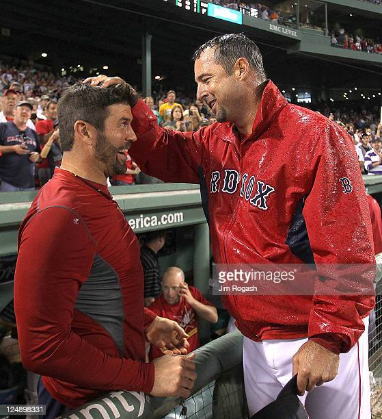 Tim Wakefield of the Boston Red Sox reacts with teammate Jason Varitek of the Boston Red Sox after earning his 200th win after a game with the...