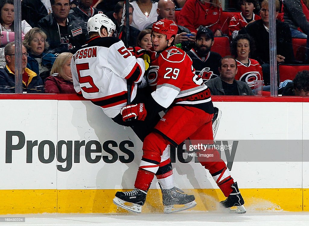 Tim Wallace #29 of the Carolina Hurricanes lands a hard hit on <a gi-track='captionPersonalityLinkClicked' href=/galleries/search?phrase=Adam+Larsson&family=editorial&specificpeople=6705080 ng-click='$event.stopPropagation()'>Adam Larsson</a> #5 of the New Jersey Devils during an NHL game on March 9, 2013 at PNC Arena in Raleigh, North Carolina.