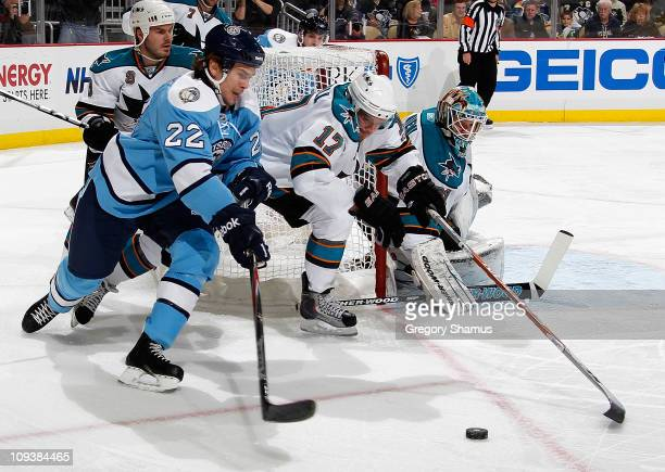 Tim Wallace of the Pittsburgh Penguins moves the puck in front of the defense of Torrey Mitchell of the San Jose Sharks on February 23 2011 at Consol...