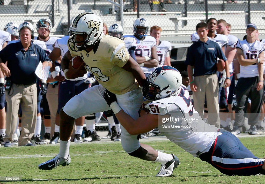 Tim Willman #51 of the Connecticut Huskies attempts to tackle Justin Holman #13 of the UCF Knights during the game at Bright House Networks Stadium on October 26, 2013 in Orlando, Florida.