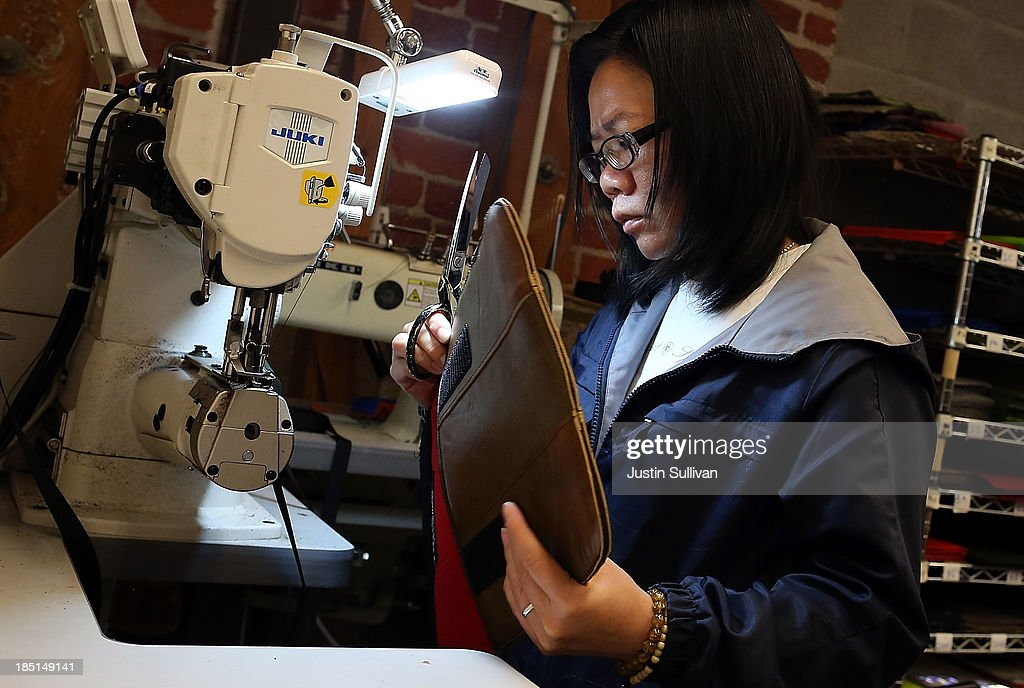 Timbuk2 worker Fang Wu sews together an iPad sleeve made of leather from R3DNA that was taken from leather seats in a salvaged luxury car at a Pick-n-Pull salvage yard on October 14, 2013 in San Fancisco, California. Sustainable design company R3DNA has partnered with Pick-n-Pull self-service auto and truck dismantlers to recover leather from seats in salvaged luxury cars, like Cadillacs and Jaguars, that will be repurposed and made into bags, iPad covers and leather jackets. The reclaimed leather is currently being integrated into bags made by San Francisco based Timbuk2. A majority of seat fabric and leather in salvaged cars ends up being shredded and discarded.