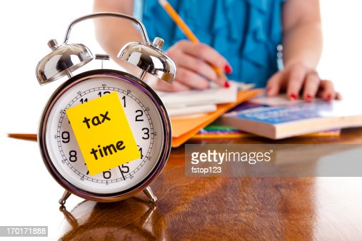 Time:  Alarm clock, income tax time note.  Woman background. Reminder.