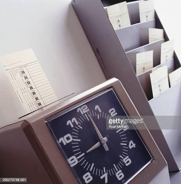 Time clock marking time card, close-up