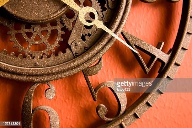 Time. Close-up of metal, rustic clock on red, rust wall.