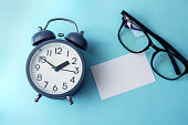 Time concept with blank white paper note copy space to add wording or message , alarm clock with reading eyeglasses decoration on blue background