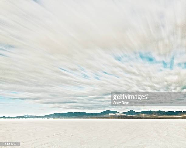 Time exposure clouds in motion above salt flats.