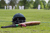 Cricket helmet, bat and ball on boundary line during a game in the English village.
