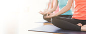 Time for yoga. Attractive young Asian woman group exercising and sitting in yoga lotus position in yoga classes