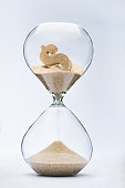 Time is money. Dollar sign flowing down in the hourglass.