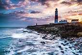 Time lapse sunset on coast with lighthouse on cliffs in Portland, Dorset, UK.