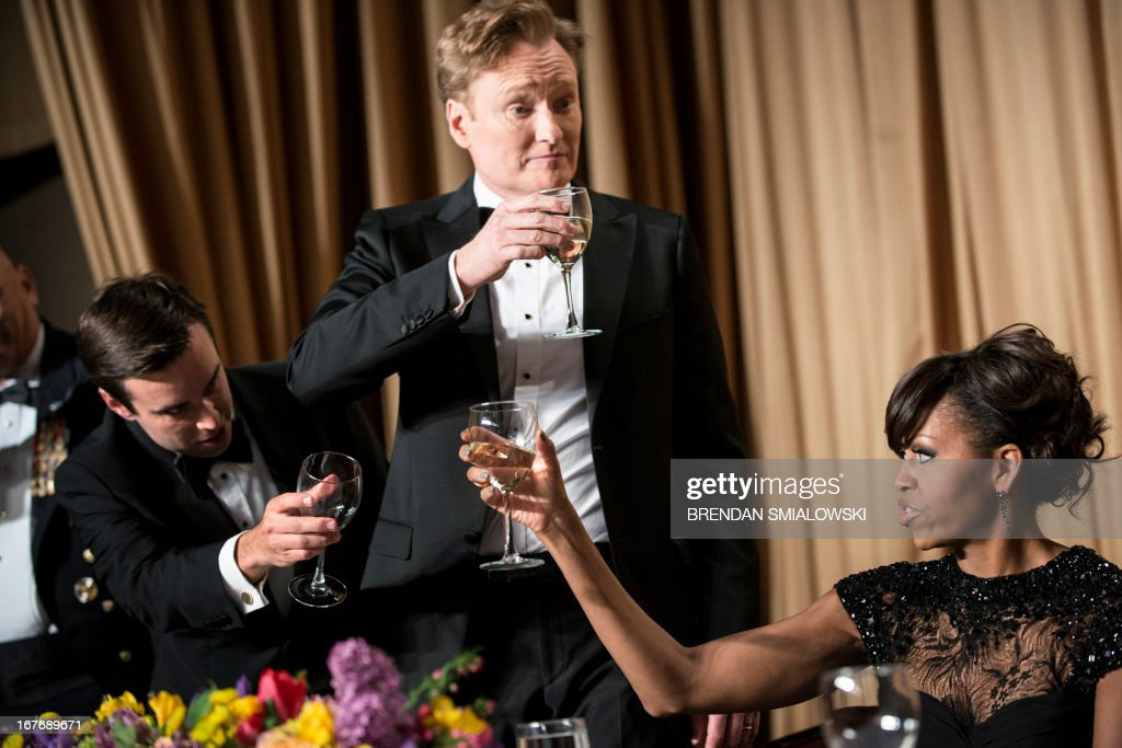 Time Magazine's Michael Scherer (L), Comedian Conan O'Brien (C) and US first lady Michelle Obama raise their glasses with others for a toast during the White House Correspondents' Association Dinner April 27, 2013 in Washington, DC. Obama attended the yearly dinner which is attended by journalists, celebrities and politicians. AFP PHOTO/Brendan SMIALOWSKI