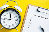 Time management concept. Alarm clock on yellow background.
