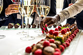 Business coworkers celebrating in a lobby.They are holding their glasses with champagne and image is focused on the african woman's hand taking a galss of champagne from the table. There is some sweet