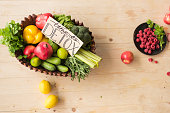 top view of time to detox card and various healthy vegetables, fruits and berries on wooden tabletop