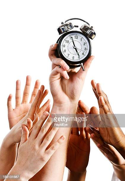 Time to go home: many hands grab alarm clock