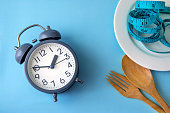 Time to lose weight , eating control or time to diet concept , alarm clock with healthy tool concept decoration on blue background