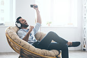 Handsome young man in headphones gesturing and keeping eyes closed while sitting in big comfortable chair at home