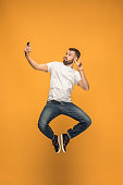 Time to take selfie. Full length of handsome young man taking selfie while jumping against orange studio background. Mobile, motion, movement, business concepts