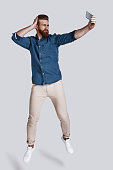 Full length of handsome young man taking selfie while jumping against grey background