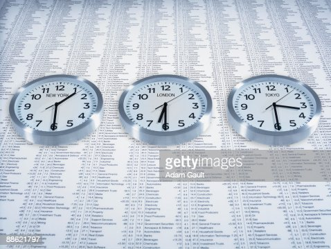 Time zone clocks on list of share prices : Stock Photo