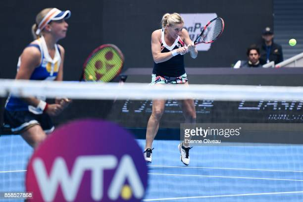 Timea Babos of Hungary and Andrea Hlavackova of the Czech Republic return a shot against Ekaterina Makarova and Elena Vesnina of Russia during their...
