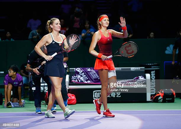 Timea Babos of Hungary and Kristina Mladenovic of France wave to the crowd after defeating Abigail Spears and Raquel KopsJones of the USA in a...