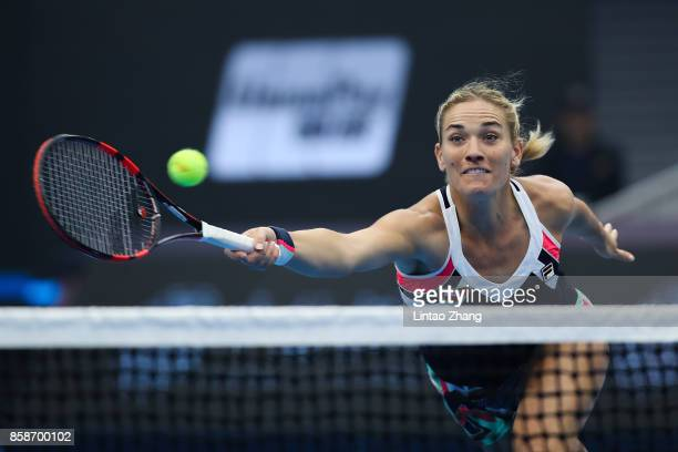 Timea Babos of Hungary returns a shot with Andrea Hlavackova of the Czech Republic against Ekaterina Makarova and Elena Vesnina of Russia during...