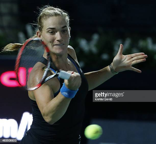 Timea Babos of Hungary returns the ball against Serbia's Jelena Jankovic during their 1st Round of the WTA Dubai Duty Free Tennis Championships on...