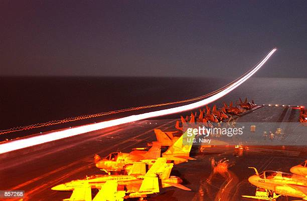 A timeexposed photograph of an F14A 'Tomcat' launching from the flight deck displays the afterburner trail as it accelerates away from the ship March...