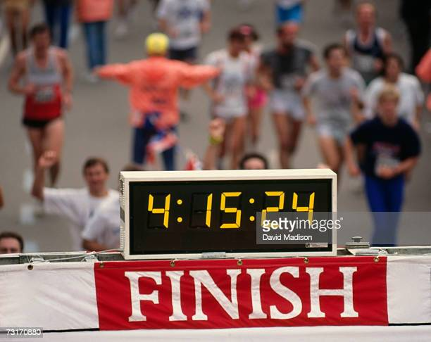 Timing clock at finish line of marathon race with runners crossing finish line