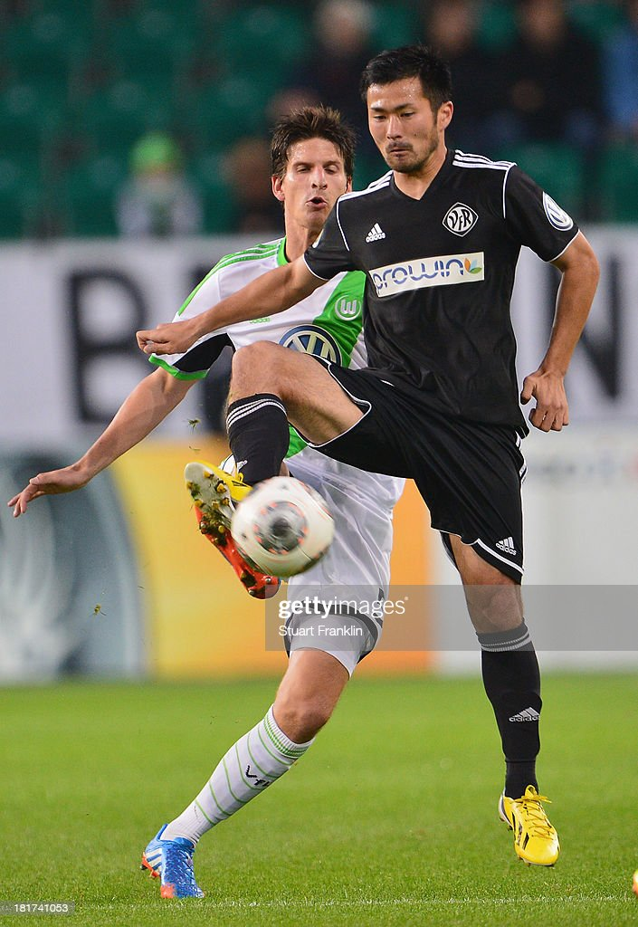 <a gi-track='captionPersonalityLinkClicked' href=/galleries/search?phrase=Timm+Klose&family=editorial&specificpeople=7864194 ng-click='$event.stopPropagation()'>Timm Klose</a> of Wolfsburg is challenged by Takuma Abe of Aalen during the second round DFB cup match between VfL Wolfsburg and Vfr Aalen at Volkswagen Arena on September 24, 2013 in Wolfsburg, Germany.