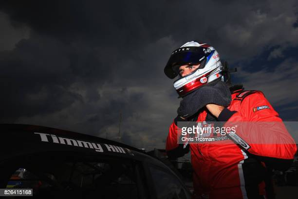 Timmy Hill driver of the OCR Gaz Bar Dodge stands in the garage area during practice for the NASCAR XFINITY Series Zippo 200 at The Glen at Watkins...