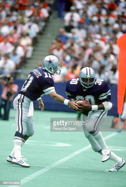 Timmy Newsome of the Dallas Cowboys takes the handoff from Danny White against the St Louis Cardinals during an NFL football game September 11 1983...