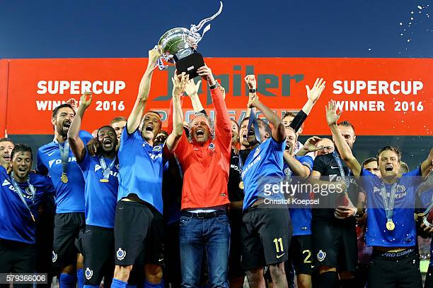 Timmy Simons and head coach Michel Preud'homme of Brugge lift the trophy after winning 21 the Supercup match between Club Brugge and Standrad Liege...