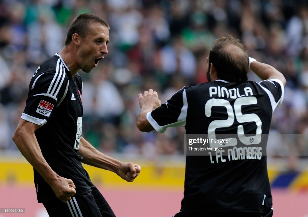Timmy Simons of Nuernberg celebrates after scoring his teams second goal with his team mate Javier Pinola during the Bundesliga match between...