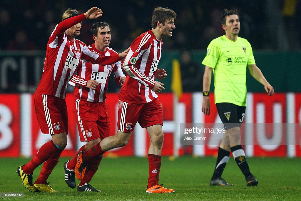 Timo Achenbachen of Aachen reacts as Thomas Mueller of Muenchen celebrates his team's third goal with team mates <a gi-track='captionPersonalityLinkClicked' href=/galleries/search?phrase=Philipp+Lahm&family=editorial&specificpeople=483746 ng-click='$event.stopPropagation()'>Philipp Lahm</a> and Anatoliy Tymoshchuk (R-L) during the DFB Cup quarter final match between Alemannia Aachen and Bayern Muenchen at Tivoli Stadium on January 26, 2011 in Aachen, Germany.