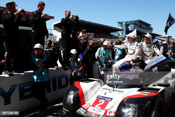 Timo Bernhard drives the winning Porsche LMP Team 919 down the pitlane with his codrivers Brendon Hartley and Earl Bamber on top after victory in the...