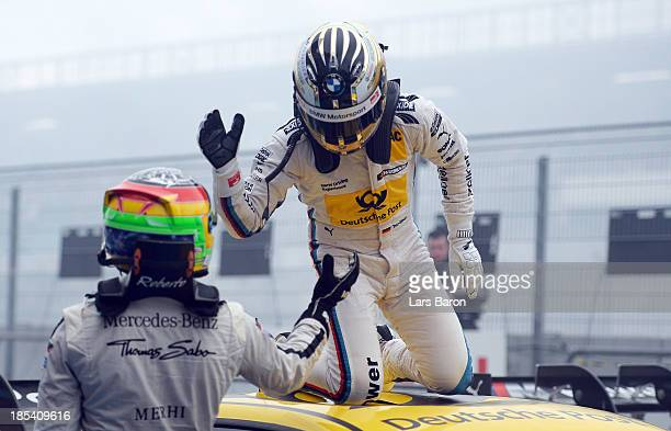 Timo Glock of Germany and BMW Team MTEK celebrates with second placed Roberto Merhi of Spain and THOMAS SABO Mercedes AMG after winning during the...