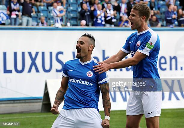 Timo Martin Gebhardt of Rostock jubilates with team mate Tommy Grupe after scoring the first goal during the third league match between FC Hansa...