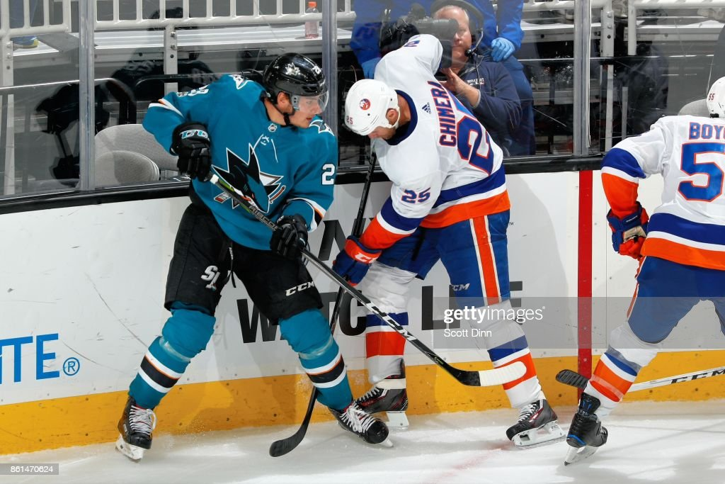 Timo Meier #28 of the San Jose Sharks and Jason Chimera #25 of the New York Islanders battle along the boards at SAP Center on October 14, 2017 in San Jose, California.
