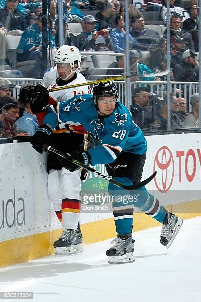 Timo Meier of the San Jose Sharks hits Jyrki Jokipakka of the Calgary Flames during a NHL game at SAP Center at San Jose on December 20 2016 in San...