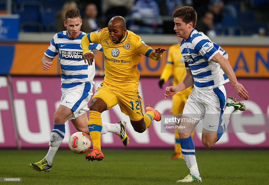 Timo Perthel (L) and Dustin Bomheuer (R) of Duisburg and Dominik Kumbela of Braunschweig compete for the ball during the Second Bundesliga match between MSV Duisburg and Eintracht Braunschweig at Schauinsland-Reisen-Arena on March 4, 2013 in Duisburg, Germany.