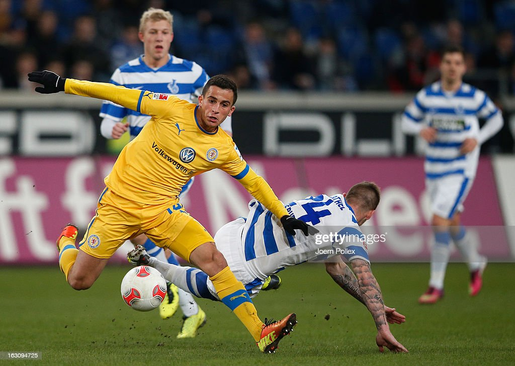 Timo Perthel (L) of Duisburg and Omar Elabdellaoui of Braunschweig compete for the ball during the Second Bundesliga match between MSV Duisburg and Eintracht Braunschweig at Schauinsland-Reisen-Arena on March 4, 2013 in Duisburg, Germany.