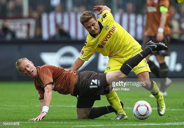 Timo Schultz of St Pauli and Mario Goetze of Dortmund battle for the ball during the Bundesliga match between FC St Pauli and Borussia Dortmund at...